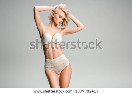 beautiful sexy girl in lingerie posing with hands on head isolated on grey with copy space #1399982417