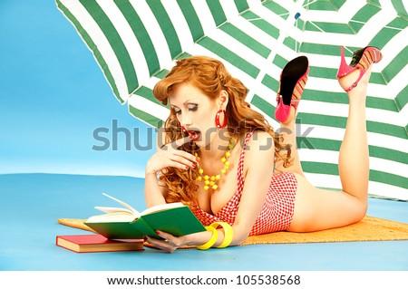 Beautiful sexy girl pin up in a pink bikini reads book on the beach under sun umbrella