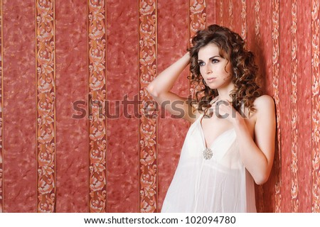 Beautiful sexy girl posing in studio looking left  leaning the wall with red wallpaper
