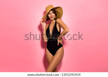 Beautiful sexy girl standing on a pink background in a colored bathing suit, smiling. Perfect for photo advertisements.