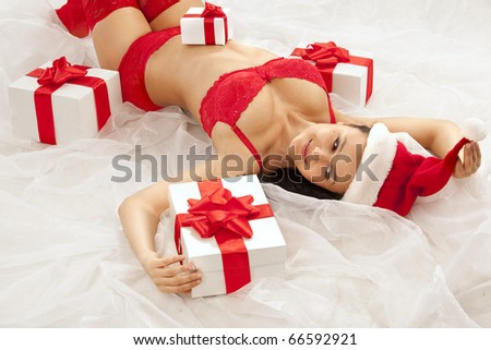 Beautiful sexy girl wearing santa hat with many gift boxes over white