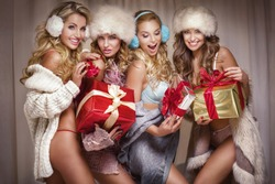 Beautiful sexy group of Santa girls. Ladies holding christmas gifts.