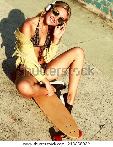 Beautiful sexy hot blonde girl smiling having fun listening music in summer outdoor in hot weather sitting on longboard lifestyle pics