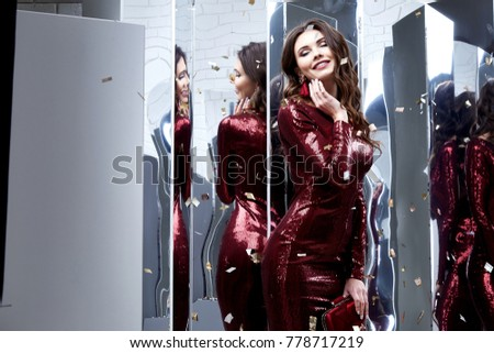 Beautiful sexy lady pretty face make-up cosmetic long brunette hairstyle beauty salon jewelry earrings woman wear skinny shiny sequins red dress party style fashion clothes for evening celebration.