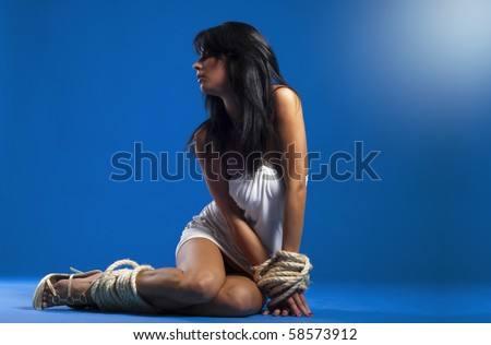 beautiful sexy lady tied with rope over blue background
