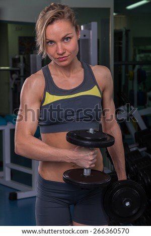 Beautiful, sexy, muscular blonde in the gym. Female fitness. Girl posing in the gym. Fitness woman doing exercises with dumbbells in the gym. Sports, bodybuilding. Attractive woman in the gym