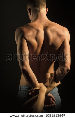Beautiful sexy naked man in jeans trousers with strong body standing with back and touching female hands on grey studio background, vertical picture