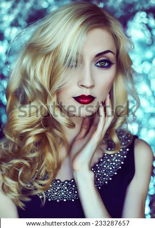 Beautiful Sexy Woman face closeup, makeup with Red Lips, green eyes and red Nails. Beauty blond Girl. Makeup, Hairdo and Manicure.Sensual Mouth. Metal  background. Snow queen concept.