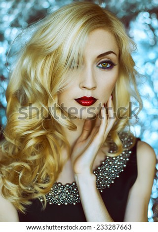 Beautiful Sexy Woman face closeup, makeup with Red Lips, green eyes and red Nails. Beauty blond Girl. Makeup, Hairdo and Manicure. Sensual Mouth. Metal  background. Snow queen concept.