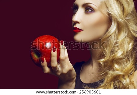 Beautiful Sexy Woman face closeup, makeup with Red Lips, Nails and red apple. Beauty blond Girl. Make up, Hairdo and Manicure. the concept of the first woman on earth (Eve).  Sexy Red Color Lips.