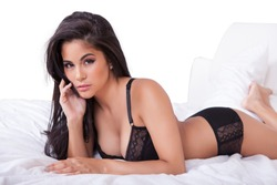 Beautiful sexy woman in black lingerie lying on her stomach on her bed with her feet in the air