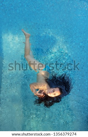 beautiful sexy woman in the best age with dark curly hair in blue bikini in sunlight floats elegantly floating happily floating in turquoise blue water in the spa pool #1356379274