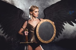 beautiful sexy woman in warrior costume and angel wings posing with shield and sword on black background