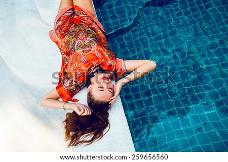 Beautiful sexy woman relaxed near pool after spa, having fun at her vacation in luxury resort, wearing stylish elegant  bright beach dress.