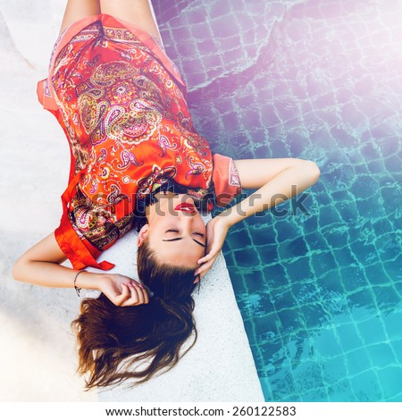 Beautiful sexy woman relaxed near pool after spa, having fun at her vacation in luxury resort, wearing stylish elegant bright beach dress. Instagram colors.
