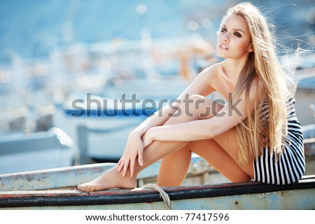 Beautiful sexy woman wearing sailor striped dress posing in boat