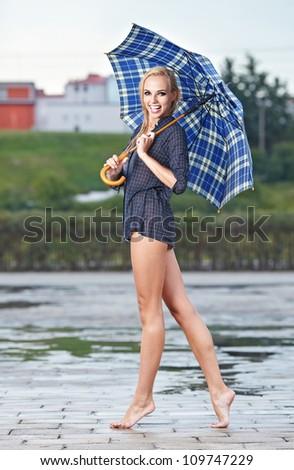 Beautiful sexy woman with blue  umbrella on rainy day