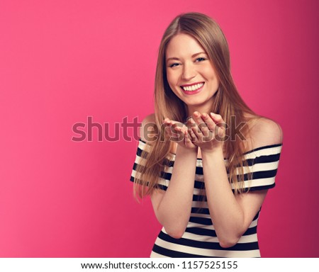 Beautiful sexy woman with enjoying eyes going to show the kissing sign the hands in fashion stripped dress on pink background. Toned closeup portrait