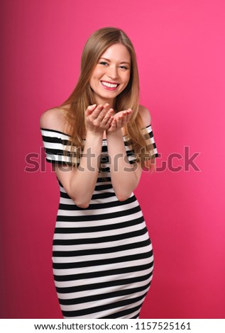Beautiful sexy woman with enjoying eyes going to show the kissing sign the hands in fashion stripped dress on pink background