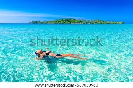 Beautiful sexy Woman with tanned skin in bikini lying on crystal clear ocean water tropical beach on background green tropic island overgrown green coconut palm trees and colorful blue sky on horizon #569050960