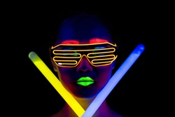 Beautiful sexy woman with UV face paint, glowing clothing, glowing bracelet in front of camera, face shot, confident look, holding light sticks. Asian woman. Party concept.