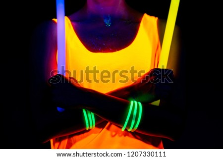 Beautiful sexy woman with UV face paint, glowing clothing, glowing bracelet in front of camera, body shot, confident look, holding light sticks. Asian woman. Party concept. #1207330111