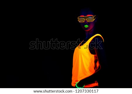 Beautiful sexy woman with UV face paint, glowing clothing, glowing bracelet in front of camera, half body shot, cool look. Asian woman. Party concept. #1207330117