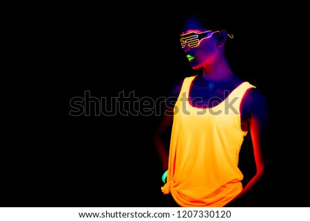 Beautiful sexy woman with UV face paint, glowing clothing, glowing bracelet in front of camera, half body shot, cool look. Asian woman. Party concept. #1207330120