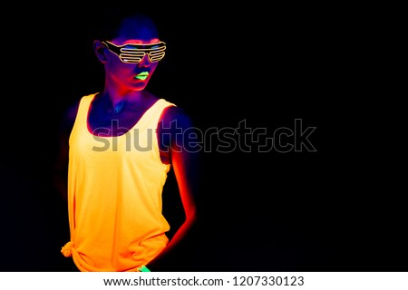 Beautiful sexy woman with UV face paint, glowing clothing, glowing bracelet in front of camera, half body shot, cool look. Asian woman. Party concept. #1207330123