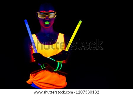 Beautiful sexy woman with UV face paint, glowing clothing, glowing bracelet in front of camera, half body shot, confident look, holding light sticks. Asian woman. Party concept. #1207330132