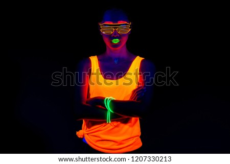 Beautiful sexy woman with UV face paint, glowing clothing, glowing bracelet in front of camera, half body shot, confident look. Asian woman. Party concept. #1207330213