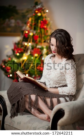 Beautiful sexy woman with Xmas tree in background reading a book sitting on chair. Portrait of a woman reading a book sitting comfortable with a blanket on legs. Attractive brunette female relaxing.