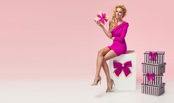 Beautiful sexy young blonde woman in pink dress sitting on a big present, holding gift box. Christmas photo, presents