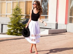 Beautiful sexy young brunette girl with long thick wavy hair thin slender figure perfect body and pretty face make-up wearing a light pink suit delicate high heels.Walk on the street in casual style