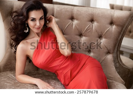 Beautiful sexy young brunette woman with long wavy hair thin slender figure perfect body and pretty face make-up wearing a red evening skinny dress and jewelry