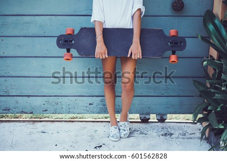 Beautiful sexy young girl in short shorts walking with longboard in sunny weather. Leisure. Healthy lifestyle. Extreme sports. Fashion look, outdoor hipster portrait, Bali, sneakers