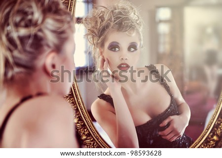 Beautiful sexy young woman near a mirror