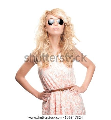 Beautiful sexy young woman standing isolated on white background. Looking into the camera and wearing sunglasses. Long wavy blonde hair.