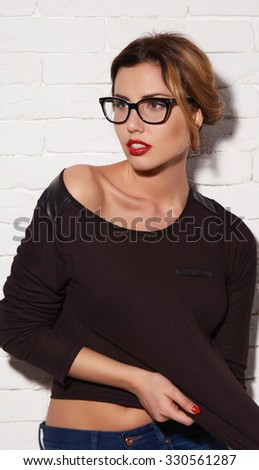 Beautiful sexy young woman with blond hair matched up with an evening make-up natural red lipstick in stylish glasses for vision wearing a black T-shirt and jeans clothed thigh ideal body shape
