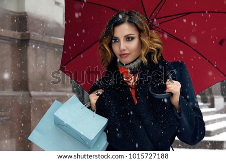Beautiful sexy young woman with curly brown hair with bright makeup wearing a black coat walking on snow-covered streets past shops with red umbrella and gift packs for Valentine's Day love