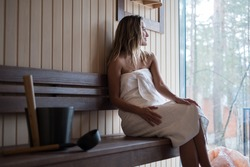 beautiful sexy young woman with white towel in the sauna . luxury interior
