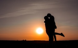 beautiful shadow of two people in love on a background of sunset