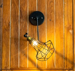 Beautiful shape lamp for decorating the house for beauty and lighting.Background is wooden texture.