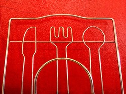 Beautiful shape wrought iron. Part of Wrought stainless steel spoon, fork and knive on red cement. Wrought iron partition.