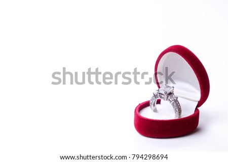 Beautiful shiny platinum engagement ring with big gem diamond in rich red velvet box isolated on white background. st Valentine's Day proposal gesture present. Copy space, front top view, background