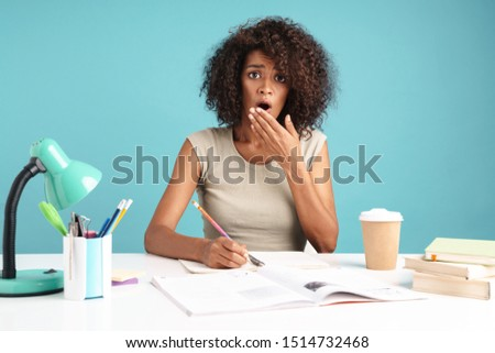 Beautiful shocked young african businesswoman casually dressed sitting at the desk isolated over blue background, studying