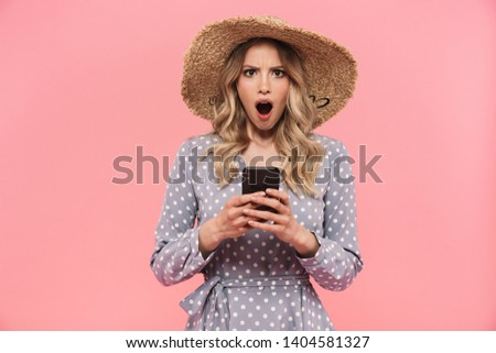 Beautiful shocked young blonde woman wearing summer hat and dress standing isolated over pink background, using mobile phone #1404581327