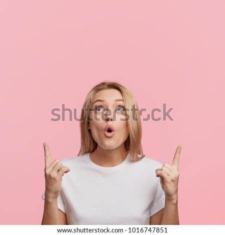 Beautiful shocked young female with blonde hair and surprised face indicates upwards, has amazed expression, isolated over pink background. Woman advertizes something on ceiling. Omg concept