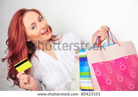 Beautiful shopping woman holding bags and credit card at a mall against white wall