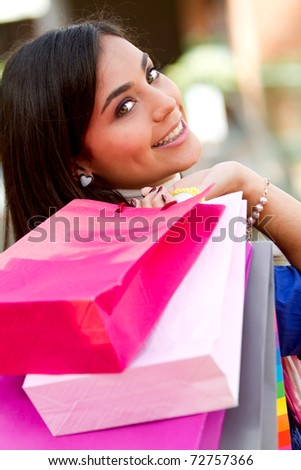 Beautiful shopping woman holding bags at a mall